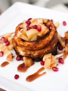 Individual mascarpone cheesecake torte with poached quince and pomegranate seeds
