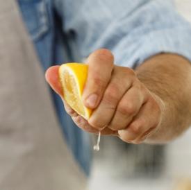 Man squeezing lemon on spring vegetables salad